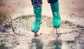 Child walking in wellies in puddle on rainy weather Stock Photography