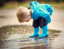 Child walking in wellies in puddle on rainy weather. Happy boy outdoors royalty free stock photography