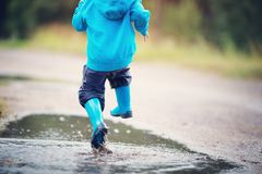 Child walking in wellies in puddle on rainy weather. Child walking in wellies and jumping in puddle on rainy weather. Boy under rain in summer outdoors royalty free stock image