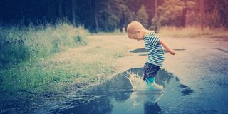 Child walking in wellies in puddle on rainy weather Royalty Free Stock Photos
