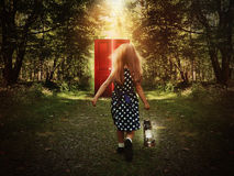 Child Walking in Woods to Glowing Red Door. A little child is walking in the woods holding a light and looking at a glowing red door on the path for a mystery or