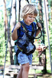 Child walks along the rope, climbing the trees, cable car. Royalty Free Stock Photos