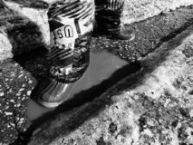 A child walks in boots through puddles in spring or winter in sunny weather. stock images