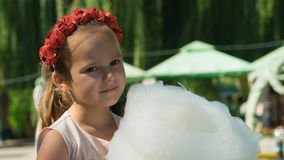 Belarus, Gomel, on March 10, 2018. Children`s holiday at the opening of the store Caravan.The girl is eating sweet airy cotton. stock image