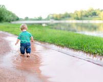 Child walks on the puddles Stock Image