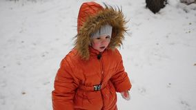 A child walks on a snowy trail in the winter park stock video