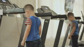 The child walks on the treadmill. The kid is exercising in the gym near the mirror. Boy cares about his body, figure, appearance and health from the childhood stock video