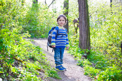 A child walks through the woods. Stock Photos