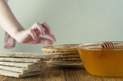 Child wants to eat a pancake. On the table is honey pancakes bread. The child wants to eat them Stock Image