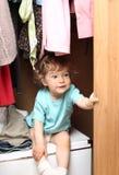 Child in wardrobe. Cute little girl hiding in wardrobe royalty free stock photography