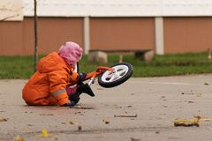 Child in a warm clothes with balance bicycle stock image