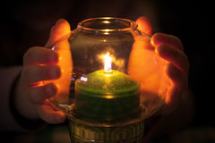 Child warm their hands at green candle. Burns in candlestick made of glass Stock Images