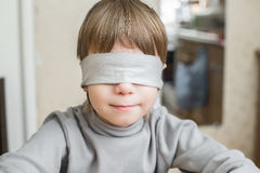 The child was blindfolded at home. Stock Photos