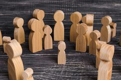 The child was lost in the crowd. A crowd of wooden figures of people surround a lost child. Lost kid. The child was lost in the crowd. A crowd of wooden figures Stock Images