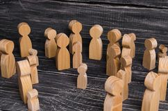 The child was lost in the crowd. A crowd of wooden figures of people surround a lost child. Lost, parents who have lost kid baby. The child was lost in the crowd Stock Photo