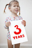 The child was three years old. A girl holding a sign with the words three years royalty free stock photos