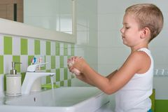 Child washing hands with soap in the bathroom. Child washing hands royalty free stock images