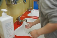 Child washing hands with soap in bathroom in kindergarten stock photography