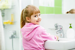 Child washing her face and hands in bathroom Royalty Free Stock Photography