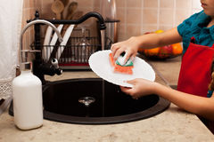 Child washing a plate with sponge at the kitchen sink, shallow d Stock Image