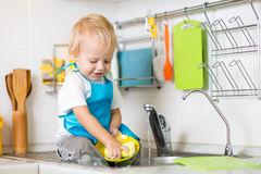 Child washing up in a domestic kitchen Royalty Free Stock Photos