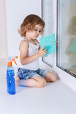 Child washing windows. Royalty Free Stock Photos
