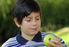 Child watch an apple before eating Stock Image