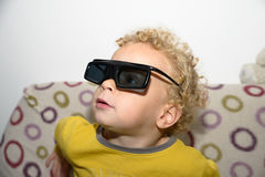 A child watches TV with 3D glasses royalty free stock photo