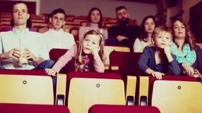 Child watching boring movie in cinema. Little girl watching boring movie in cinema house Stock Image