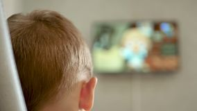 A child is watching a cartoon sitting on a chair. The TV screen is out of focus. 4k stock video footage