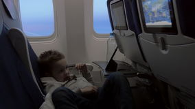 Child watching cartoon on smartphone in airplane. Boy in earphones lying on the seats in airplane and watching movie or cartoon on smart phone. Entertainment stock video footage