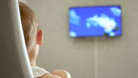The child is watching a cartoon. The TV screen is out of focus. 4k stock footage