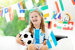 Kids watch football game. Child watching soccer. Child watching football game on tv. Girl in Argentina jersey watching soccer game during championship. Kid fan Royalty Free Stock Photography