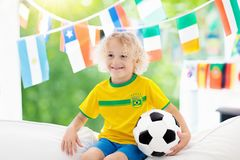 Fans watch football game. Child watching soccer. Child watching football game on tv. Little boy in Brazil tricot watching soccer game during championship. Kid Stock Photo