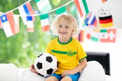 Fans watch football game. Child watching soccer. Child watching football game on tv. Little boy in Brazil tricot watching soccer game during championship. Kid Royalty Free Stock Photo