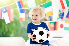 Kids watch football game. Child watching soccer. Child watching football game on tv. Little boy in France tricot watching soccer game during championship. Kid Royalty Free Stock Photo