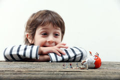 Child watching miniature people breaking an egg Royalty Free Stock Photos