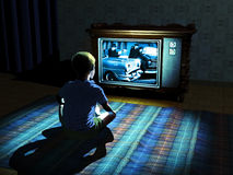 Child watching television. Young boy in the sixties, sat in front of the television, at night,  watching a detective movie Stock Photo