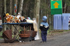 A child watching a toy stall. Wicker baskets, Bialowieza Forest. Object of desire. Children's dreams Royalty Free Stock Image