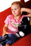Child watching TV. Little girl sits with bear on the sofa and watches TV, holding pilot Stock Photo