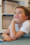 Child watching tv. Smiling young boy watching television lying on th carpet and resting his chin on hand Royalty Free Stock Images