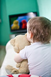 Child watching TV. Kid with teddy bear watching TV Stock Photo