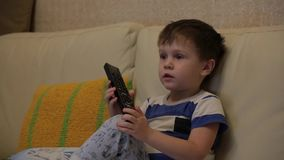 The child is watching TV. In his hands the remote control. The little boy switches channels on the TV stock video