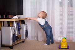 Child watching TV. Little girl standing in front of TV Stock Image