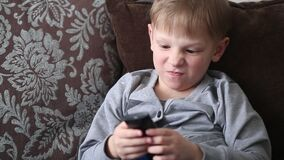 The child is watching TV and switching channels by remote control. The child is watching TV and switching channels by remote control stock video footage