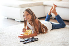 Child watching tv. 8 years old child watching tv laying down on a white carpet at home alone Royalty Free Stock Photo