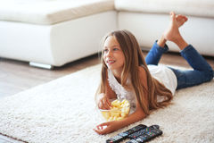 Child watching tv. 8 years old child watching tv laying down on a white carpet at home alone Stock Photo