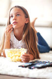 Child watching tv. 8 years old child watching tv laying down on a white carpet at home alone Stock Images