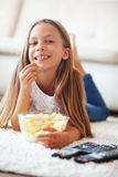 Child watching tv. 8 years old child watching tv laying down on a white carpet at home alone Stock Photography