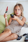 Child watching tv. 7 years old child watching tv sitting on sofa at home Stock Photography